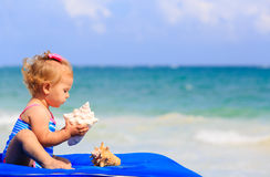 Śliczna mała dziewczynka z seashells na plaży Zdjęcie Stock