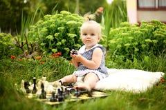 Śliczna mała dziewczynka z szachy w lato ogródzie Obrazy Stock