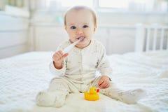 Śliczna mała dziewczynka z toothbrush w pyjamas na łóżku obraz royalty free