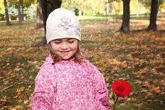 Śliczna mała dziewczynka z wzrastał w autmn parku Obraz Royalty Free