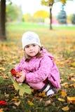 Śliczna mała dziewczynka z wzrastał w autmn parku Obrazy Stock