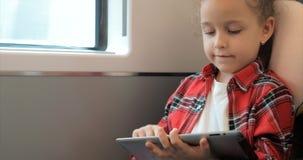 Śliczna mała dziewczynka zabawia z pastylką Dziecko wydaje wolnego czas, przejażdżki elektryczny pociąg, bawić się mobilną grę we zbiory