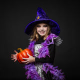 Śliczna mała Halloweenowa czarownica trzyma pomarańczowej bani Zdjęcie Stock