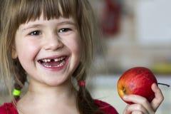 Śliczna mała kędzierzawa bezzębna dziewczyna uśmiecha się czerwonego jabłka i trzyma Obrazy Stock