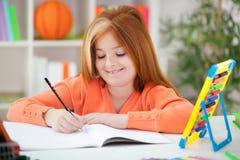 Śliczna mała miedzianowłosa dziewczyna robi jej pracie domowej w domu Obraz Royalty Free