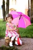 Śliczna mała piękna dziewczyna z różowym parasolem i torebką w parku Obraz Royalty Free