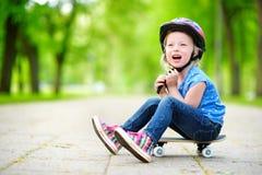 Śliczna mała preteen dziewczyna jest ubranym hełma obsiadanie na deskorolka zdjęcie royalty free