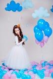 Śliczna mała princess dziewczyny pozycja wśród balonów w pokoju nad białym tłem patrzeć kamerę Dzieciństwo Obrazy Stock