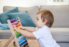Śliczna mała szczęśliwa chłopiec bawić się z kolorowym abakusem zdjęcia royalty free