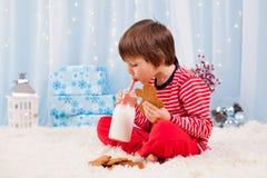 Śliczna mała szczęśliwa chłopiec je ciastka i pije mleko, czeka Obraz Royalty Free