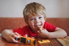 Śliczna mała uśmiechnięta chłopiec z blondynem w czerwonej koszula W rękach i obok on są zabawki Ranku dom fotografia stock