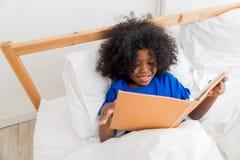 Śliczna małe dziecko amerykanina afrykańskiego pochodzenia dziewczyna czyta książkę obraz royalty free