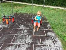 Śliczna małe dziecko chłopiec ma zabawę przy parkiem z huśtawką obraz royalty free