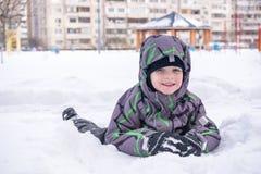 Śliczna małe dziecko chłopiec w kolorowej zimie odziewa kłaść w dół dalej Aktywnego outdoors czas wolny z dziećmi wewnątrz szczęś Zdjęcia Stock