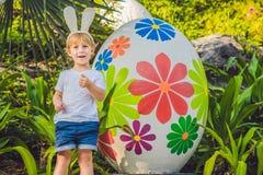 Śliczna małe dziecko chłopiec z królików ucho ma zabawę z tradycyjnymi Wielkanocnymi jajkami tropi, outdoors r Berbeć fi fotografia stock