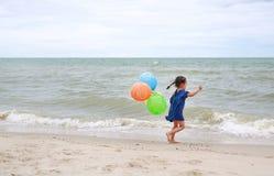 Śliczna małe dziecko dziewczyna bawić się balony na plaży zdjęcie stock