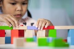 Śliczna małe dziecko dziewczyna bawić się z kolorowymi drewnianymi blokami obrazy royalty free