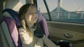 Śliczna małej dziewczynki jazda w samochodzie przy tylnym siedzeniem i patrzeć szczęśliwy zbiory wideo