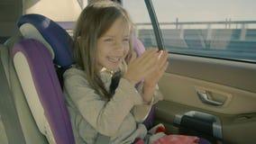 Śliczna małej dziewczynki jazda w samochodzie przy tylnym siedzeniem i patrzeć szczęśliwy zdjęcie wideo