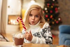 Śliczna małej dziewczynki mienia cukierku trzcina, seansu kciuka up gest, l Obrazy Stock