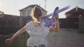 Śliczna małej dziewczynki pozycja w jardzie trzyma zabawkarskiego samolot w jej ręce Dziecka narządzanie wszczynać zabawkarskiego zdjęcie wideo