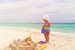 Śliczna małej dziewczynki sztuka z piaskiem na plaży Fotografia Stock