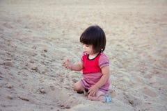 Śliczna małej dziewczynki sztuka z piaskiem na plaży zdjęcia stock