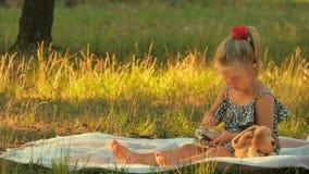 Śliczna małej dziewczynki sztuka z pieniądze na koc i zbiera je w słój zdjęcie wideo