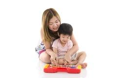 Śliczna matka uczy jej syna dzieciaka bawić się elektrycznego zabawkarskiego pianino Zdjęcie Stock