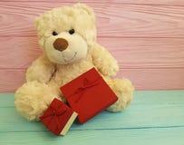 Śliczna miś zabawka z czerwieni pudełka menchiami i błękitny drewnianym Zdjęcie Stock