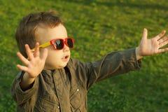 Śliczna miedzianowłosa chłopiec w okularach przeciwsłonecznych dosięga out zmierzch obraz royalty free