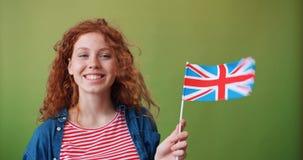 Śliczna miedzianowłosa dziewczyna trzyma Brytyjski flagę na zielony tła ono uśmiecha się zbiory wideo