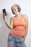 Śliczna millennial dziewczyna uśmiecha się mądrze telefon i używa obraz royalty free