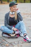 Śliczna modna kobieta relaksuje z jej łyżwową deską Zdjęcia Royalty Free