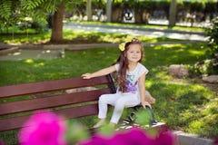 Śliczna muzykalna dziecka dziecka dziewczyna z brunetek hairs i elegancką odzieżą cieszy się życia obsiadanie na drewnianej krzes Zdjęcie Stock