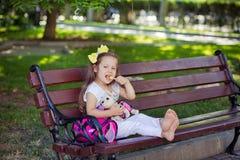 Śliczna muzykalna dziecka dziecka dziewczyna z brunetek hairs i elegancką odzieżą cieszy się życia obsiadanie na drewnianej krzes Zdjęcie Royalty Free