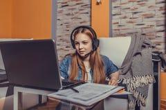 Śliczna nastoletnia dziewczyna jest ubranym hełmofony online i ma wideokonferencję z laptopem fotografia stock