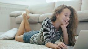 Śliczna nastoletnia dziewczyna na dywanie pracuje z laptopem Steadicam strzelał szczęśliwa nastoletnia dziewczyna blisko kanapy z zbiory wideo