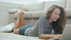Śliczna nastoletnia dziewczyna na dywanie pracuje z laptopem Steadicam strzelał szczęśliwa nastoletnia dziewczyna blisko kanapy z zbiory