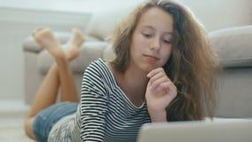 Śliczna nastoletnia dziewczyna na dywanie pracuje z laptopem Steadicam strzelał szczęśliwa nastoletnia dziewczyna blisko kanapy z zdjęcie wideo