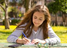 Śliczna nastoletnia dziewczyna pisze notatkach na papierowym ochraniaczu drewnianym stołem na zielonej łące obrazy royalty free