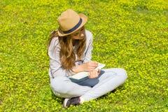 Śliczna nastoletnia dziewczyna pisze notatkach na papierowym ochraniaczu na zielonej łące Selekcyjna ostro?? fotografia stock