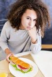 Śliczna nastoletnia dziewczyna z kędzierzawym włosy ma łasowanie problem obraz royalty free