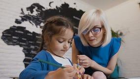 Śliczna nauczyciel mama pracuje z pięknym kreatywnie dzieciakiem przy szkołą podstawową Nauczyciela obsiadanie przy biurkiem obok zbiory