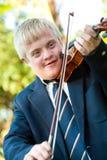 Śliczna niepełnosprawna chłopiec bawić się skrzypce. obraz royalty free