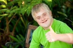 Śliczna niepełnosprawna chłopiec pokazuje aprobaty outdoors. Zdjęcia Royalty Free