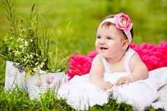 Śliczna nowonarodzona dziewczyna ono uśmiecha się na trawie obraz stock