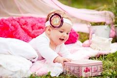Śliczna nowonarodzona dziewczyna ono uśmiecha się na trawie zdjęcia stock