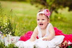 Śliczna nowonarodzona dziewczyna ono uśmiecha się na trawie obrazy stock