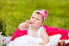 Śliczna nowonarodzona dziewczyna ono uśmiecha się na trawie obraz royalty free